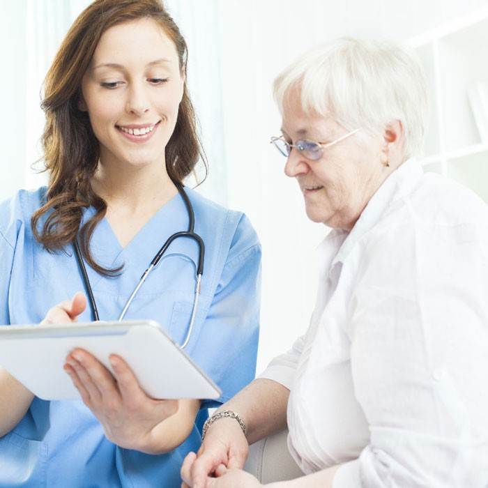 A doctor consults with a senior woman patient
